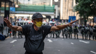 A man tells demonstrators to back away from a stand off against police line during a protest in the Central district of Hong Kong.