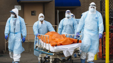Medical workers in protective clothing move the body of a deceased patient to a refrigerated overflow morgue outside the Wyckoff Heights Medical Center in the Brooklyn borough of New York.