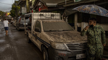 A police vehicle is covered in ash mixed with rainwater after the eruption.