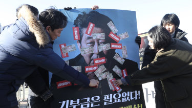 South Korean protesters attach fake Japanese banknotes on an image of Japanese Prime Minister Shinzo Abe during a rally denouncing a bill on Japan's wartime forced labour, which is being pushed by South Korea's parliamentary speaker in front of the National Assembly in Seoul.