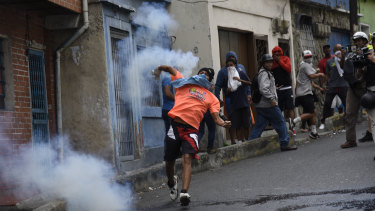 A demonstrator throws back a tear gas canister during a protest in the Cotiza neighbourhood of Caracas on Monday.