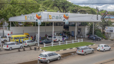Customers queue at a petrol station in Harare.