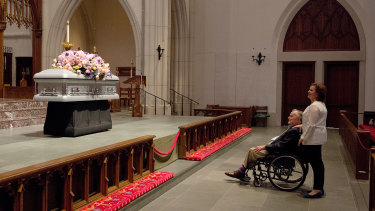 Former president George H.W. Bush looks at the casket of his wife.
