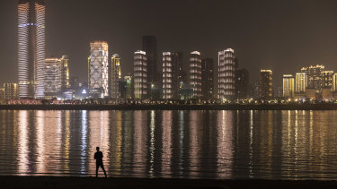 A man looks across to illuminated buildings on the other side of the Yangtze River at night in Wuhan, Hubei, China.