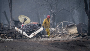 A firefighter searches a burned-out building in Paradise, California.