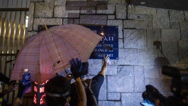 A demonstrator spray paints a sign displayed outside the Wong Tai Sin Police Station during protests in the Wong Tai Sin district of Hong Kong.