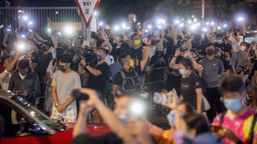 Supporters illuminate mobile phone torches outside the headquarters of the Apple Daily.