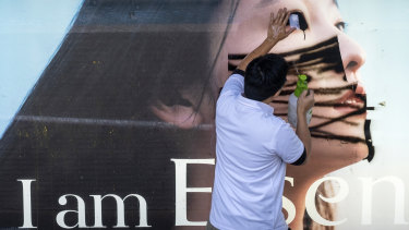 A worker cleans a spray painted mask on an advertisement at a bus station in the Central district of Hong Kong on Monday.