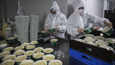 Workers in protective coveralls, masks and gloves handle dry and hot noodle containers at a noodle factory in Wuhan, Hubei Province, China.