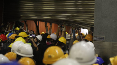 Demonstrators hold up a damaged shutter after breaking into the Legislative Council building.