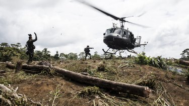 Anti-Narcotics police officers guide a police helicopter to land over a coca field during an operation in Tumaco, Colombia, last year.
