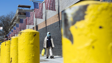 A person wearing a protective mask walks outside the Elmhurst Hospital Centre in the Queens borough of New York.
