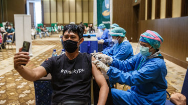 A healthcare worker is injected with the vaccine in Bali.