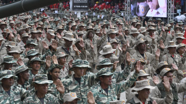 """National Bolivarian Militia members raise their hands during a military parade on """"National Bolivarian Militia Day"""" at Los Proceres in Caracas, Venezuela."""