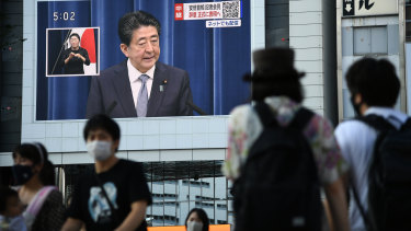 Pedestrians walk past a screen displaying a live broadcast of Prime Minister Shinzo Abe speaking on Friday.