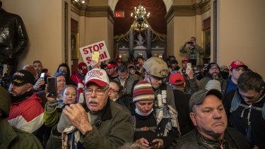 Para perusuh berjalan melewati pintu gedung Capitol AS saat Kongres bertemu untuk mengesahkan hasil pemilu.