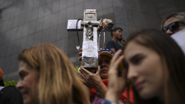A demonstrator holds a cross during a protest on the sidelines of the visit by Michelle Bachelet, high commissioner for human rights at the UN.