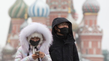 Tourists wear protective face masks as they walk in Red Square near the Kremlin in Moscow, Russia.