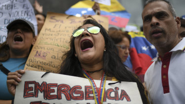 Demonstrators shout slogans during a protest on the sidelines of a visit by Michelle Bachelet in Caracas.