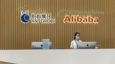 The Ant Group Co. logo and the Alibaba Group Holding Ltd. logo are displayed behind a reception desk at the company's headquarters in Hangzhou, China.