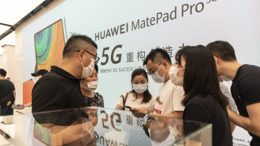 Customers wearing protective masks stand in front of an advertisement for Huawei.