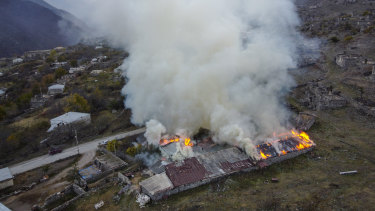 Smoke rises from a burning house in an area once occupied by Armenian forces but soon to be turned over to Azerbaijan, in Karvachar, the separatist region of Nagorno-Karabakh.