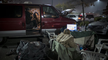 A Camp Fire evacuee plays with a dog in a vehicle, left, while a woman watches television as they camp in a Walmart Inc. store parking lot in Chico, California.