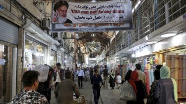 People walk at the old main bazaar in Tehran, where the effects of the sanctions can be easily felt.