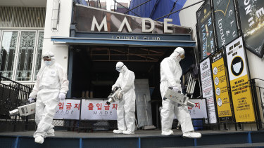 Workers spray disinfectant in Seoul.
