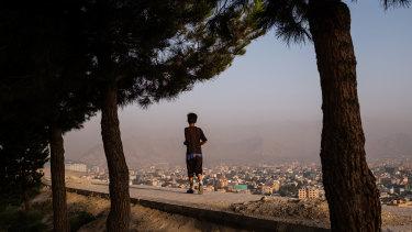 A boy runs along a wall at the top of Bibi Mahru Hill in Kabul, Afghanistan.