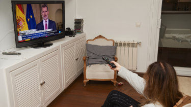 A woman watching King Felipe VI's speech at home in Madrid, Spain.