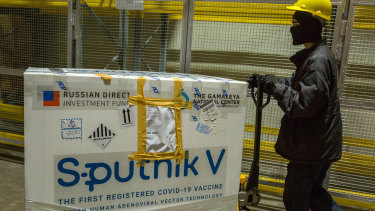 A worker uses a pallet trolley to transport a crate of the Sputnik V COVID-19 vaccine at a cold storage facility in Karachi, Pakistan.