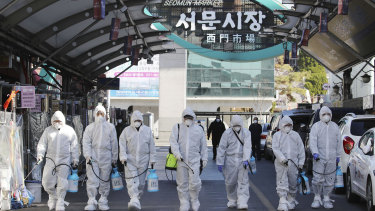 Workers spray disinfectant as a precaution against the COVID-19 at a local market in Daegu in South Korea.