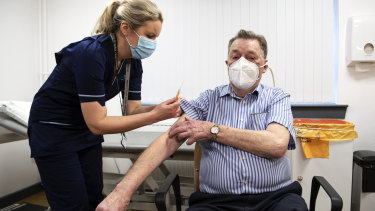 A nurse administers the AstraZeneca vaccine to a man in Dundee, Scotland, on January 4.