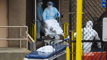 Medical workers in protective clothing move the body of a deceased patient to a refrigerated overflow morgue outside the Wyckoff Heights Medical Centre in Brooklyn, New York.