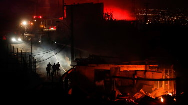 People walk away from a burning house in Valparaiso, Chile. The picturesque town has lost at least 120 homes in the Christmas Eve/Day fires.
