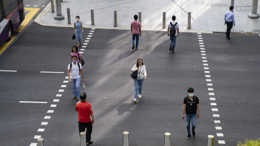 People keep their distance while crossing a road in Singapore to curb the spread of COVID-19.