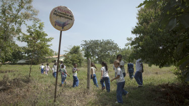 """Children walk past a sign reading in Spanish """"Danger presence of hippos"""" as they arrive for class at a school near the Napoles Park in Puerto Triunfo."""