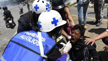 Medical personnel give first aid to a protester during a military uprising in Caracas, Venezuela.