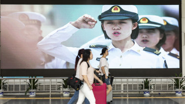 Travellers walk past an advertisement for the People's Liberation Army (PLA) on a screen near the Luohu border crossing in Shenzhen, China.