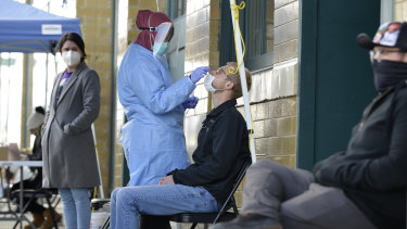 A medical staff member performs a Covid-19 test outside the Family Healthcare building in downtown Fargo, North Dakota.