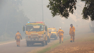 Firefighters are seen near fires at Lake Cooroibah Road and Jirrimah Crescent in Cooroibah on Saturday.