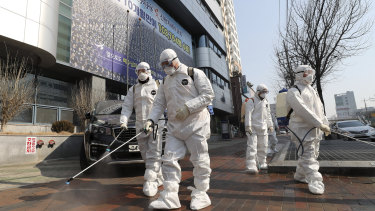 Medical workers spray disinfectant in front of a church in Daegu, South Korea.