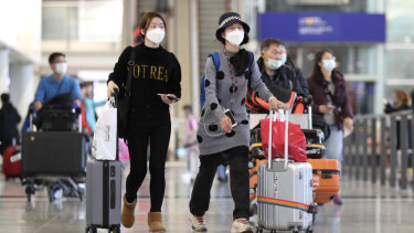 Travellers wearing face masks walk through the check-in hall at Hong Kong International Airport.