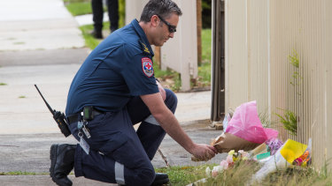 A paramedic lays flowers at the scene on Friday.