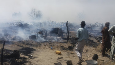 People check the remnants of houses destroyed by extremists in Monguno, Borno state, Nigeria, last year.