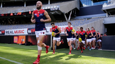 Leading man: Melbourne skipper Max Gawn runs out with his team at Optus Stadium in Perth on Sunday.