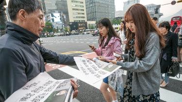 A commuter picks up a copy of the Munhwa Ilbo newspaper featuring an image of the Moon and Kim in Seoul.