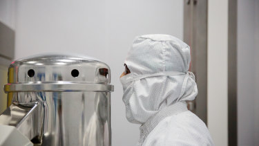 An employee at a pharmaceutical plant in India monitors machinery compressing generic pills for HIV patients.