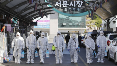 Workers spray disinfectant as a precaution against the COVID-19 at a local market in Daegu, as the country raises the alert level.